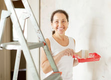 Happy mature woman paints wall Stock Photos