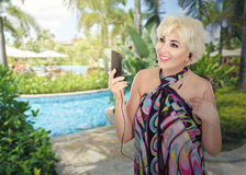 Happy mature woman in pareo posing on pool background Stock Photos