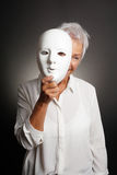 Happy mature woman peeking from behind mask stock images