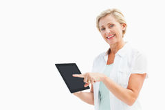 Happy mature woman pointing to tablet pc Royalty Free Stock Image