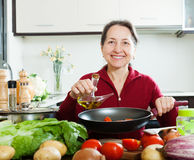 Happy mature woman pouring oil into fryingpan Royalty Free Stock Photography