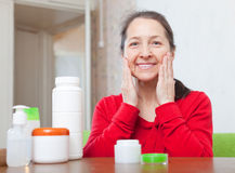 Happy mature woman puts cream on face Stock Images