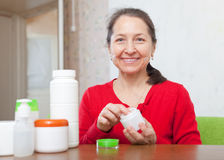 Happy mature woman puts cream on face Royalty Free Stock Image