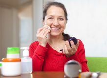 Happy mature woman puts facepowder Stock Images