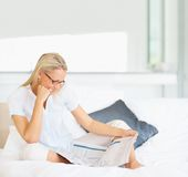 Happy mature woman reading a newspaper on bed Stock Photo