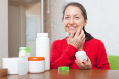 Happy mature woman in red doing cosmetic mask Royalty Free Stock Photo