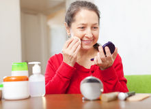 Happy mature woman in red puts facepowder Royalty Free Stock Images