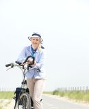 Happy mature woman relaxing with bike on a summer day Royalty Free Stock Photo