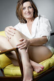 Happy mature woman relaxing on chair. Royalty Free Stock Images