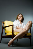Happy mature woman relaxing on chair. Royalty Free Stock Photography