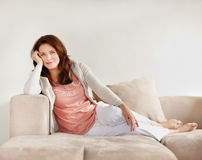 Happy mature woman relaxing on couch Stock Photo