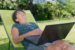 Happy mature woman relaxing resting on the deck chair in garden Royalty Free Stock Photos