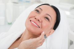Happy mature woman relaxing at spa. Close up portrait of delighted senior lady touching her face. She is lying on daybed in beauty salon and smiling Stock Image