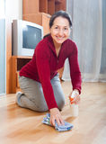 Happy mature  woman rubbing wooden floor Stock Images