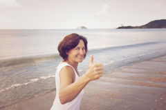 Happy mature woman running on the beach. Happy mature woman running and smiling on the beach Royalty Free Stock Images
