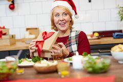Opening box. Happy mature woman in Santa cap opening giftbox with xmas present by festive table Stock Image