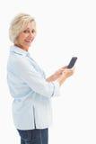 Happy mature woman sending a text Stock Photo