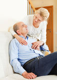 Happy mature woman with senior husband on sofa Stock Image