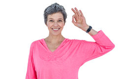 Happy mature woman showing OK sign. Against white background royalty free stock photography