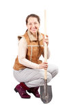 Happy mature woman sits with spade Royalty Free Stock Image
