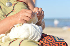 Happy mature woman sitting on beach and knitting Stock Photos