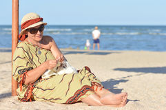 Happy mature woman sitting on beach and knitting on summer outdoors background Stock Photo