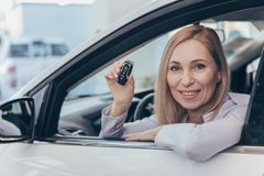 Mature businesswoman choosing new automobile at the dealership royalty free stock image