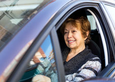 Happy mature woman sitting in new car Stock Image