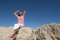 Happy Mature Woman sitting on Rocks royalty free stock photography