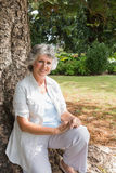 Happy mature woman sitting on tree trunk Royalty Free Stock Images