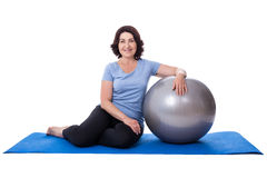 Happy mature woman sitting on yoga mat with fitness ball isolate Stock Photo