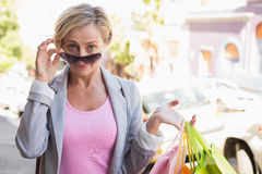 Happy mature woman smiling at camera with her shopping purchases Stock Image