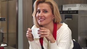 Happy mature woman smiling having coffee resting after cooking at the kitchen. Sliding shot of a beautiful mature happy woman smiling to the camera relaxing at stock photos