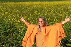 Happy mature woman with spread arms in flower field. Happy mature woman with orange shawl spread her arms in a flower field Royalty Free Stock Photo