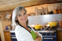 Happy mature woman standing with arms crossed in kitchen Stock Images