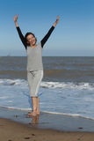 Happy mature woman standing in the sea. Mature woman enjoying the sea and stretching her arms Royalty Free Stock Photography