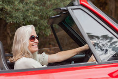 Happy mature woman with sunglasses driving red convertible Royalty Free Stock Image