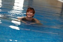 Happy mature woman in swimming pool Royalty Free Stock Photo