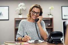 Happy mature woman talking on phone. Beautiful mature woman talking on phone at creative office. Happy smiling businesswoman answering telephone at office desk royalty free stock images