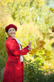 Happy mature woman throwing  maple leaves Stock Photography