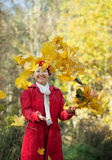 Happy mature woman throwing yellow  leaves Stock Images