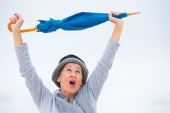 Happy mature woman with umbrella arms up Royalty Free Stock Photos