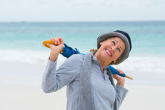 Happy mature woman with umbrella beach background Stock Photos