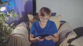 Happy mature woman using credit card and phone at home. 4K stock video