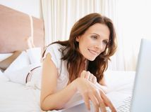 Happy mature woman using laptop on bed Royalty Free Stock Photos