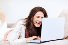 Happy mature woman using laptop on couch Royalty Free Stock Photos