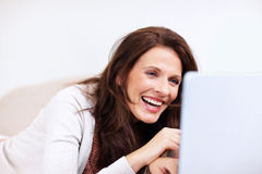 Happy mature woman using a laptop at home Stock Image