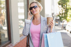 Happy mature woman walking with her shopping purchases Royalty Free Stock Photos