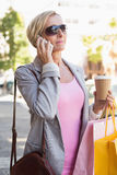 Happy mature woman walking with her shopping purchases Stock Photo