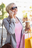 Happy mature woman walking with her shopping purchases Royalty Free Stock Photo